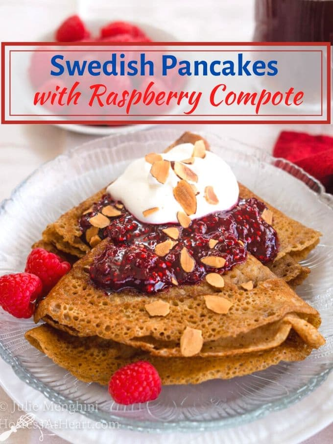 "A folded Swedish Pancake on a glass plate loaded with a red raspberry compote and whipped topping. Three red raspberries sit next to the pancake. The title ""Swedish Pancakes with Raspberry Compote\"" appears over the top of the photo."