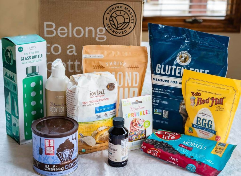 Side facing photo of products purchased from Thrive Market including flour, chocolate chips, vanilla, lotion, a glass bottle, and sprinkles