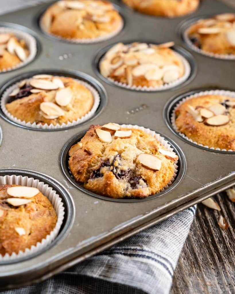 An angled closeup of a muffin tin filled with baked cherry almond muffins topped with shaved almonds sitting on a striped blue napkin over a weathered wood board.