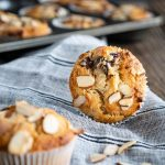 Front facing photo of a baked cherry almond muffin sitting on it side showing the top of the muffin sprinkled with sliced almonds on a blue stripped napkin. A blurred muffin is in the front to the side and additional almonds are sprinkled over the napkin