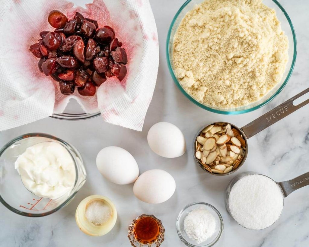 Top down photo of the ingredients used to make cherry almond muffins including almond flour, sour cream, baking powder, sugar, eggs, vanilla, cherries and salt.