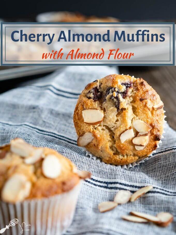 Front facing photo of a baked cherry almond muffin sitting on it side showing the top of the muffin sprinkled with sliced almonds on a blue stripped napkin. A blurred muffin is in the front to the side and additional almonds are sprinkled over the napkin.The title banner runs across the top.