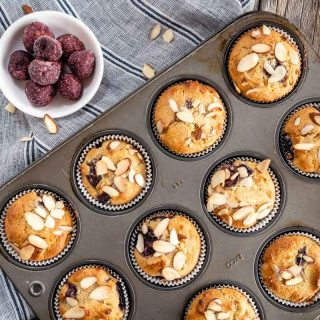 A top-down view of a tray of Cherry Almond Muffins and bowl of Frozen Cherries over a blue striped napkin.