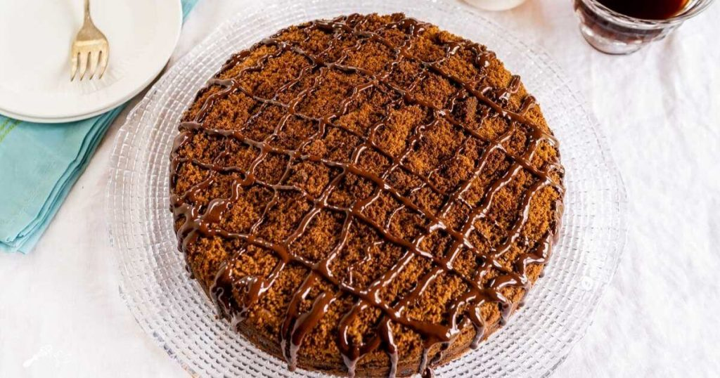 Top down view of a chocolate coffee cake topped with cinnamon streusel and drizzled with dark chocolate sitting on a glass plate over a white table cloth. A pretty turquoise napkin and two white plates with a fork sit to one side and a cup of coffee sits on the other.
