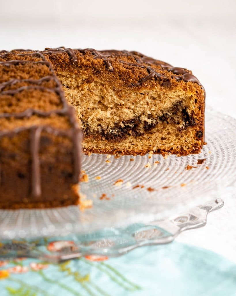 Side view of a Chocolate Coffee Cake with Sour Cream sitting on a glass cake plate. A piece has been removed showing the layer of dark chocolate that runs through it. The cake is topped with a cinnamon streusel and drizzled with more chocolate.