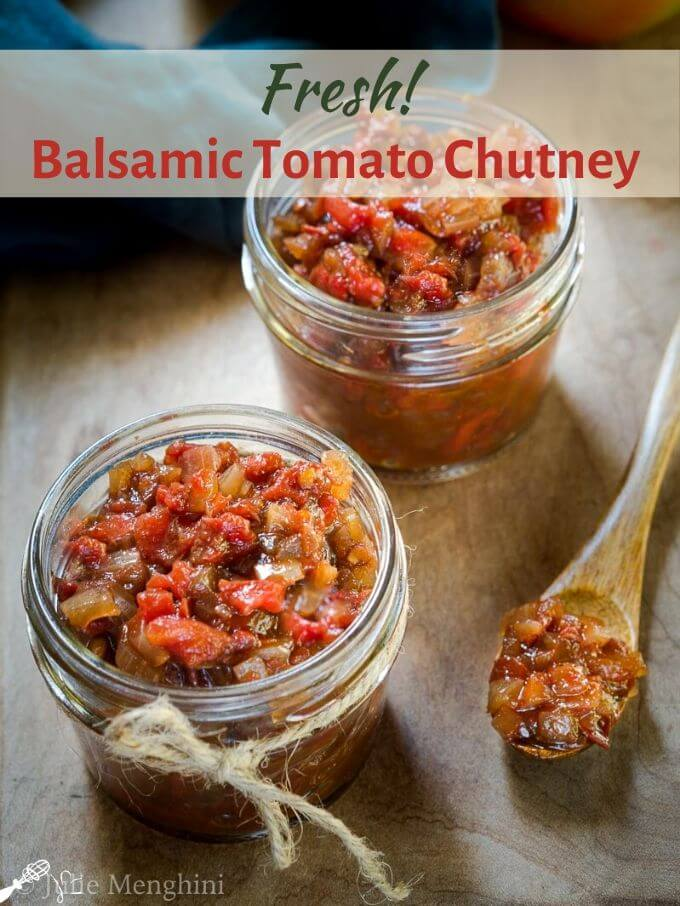 Small jar with a jute string around it filled with Balsamic Tomato Chutney. A wooden spoon filled with chutney sits beside it on a wooden cutting board. The title runs across the top of the photo.