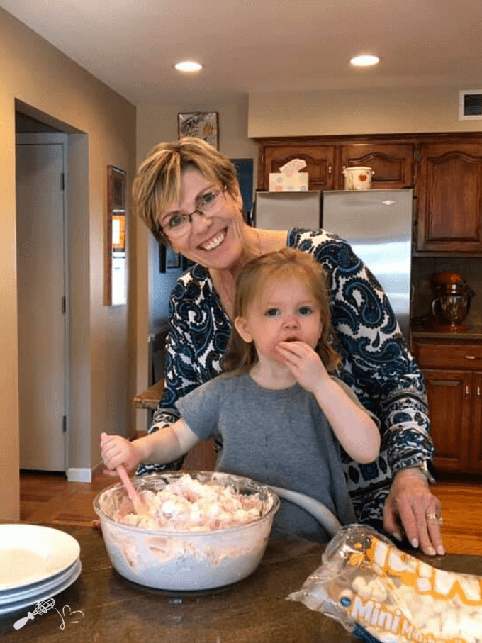 Photo of myself with my granddaughter making a big bowl of pink fluff. She's eating the marshmallows instead of stirring them into the bowl of fluff.