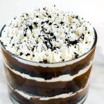 Top angle photo of a chocolate cake trifle showing several layers of cake, pudding, whipped cream and cookie crumbs in a tall trifle bowl.