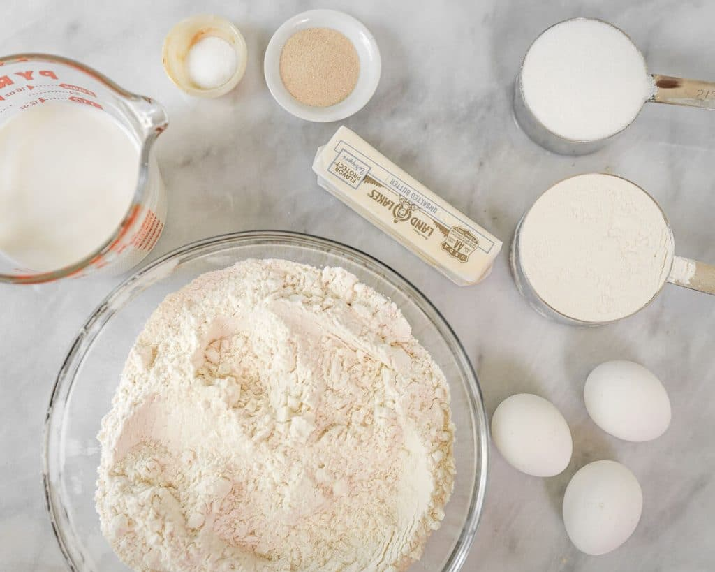 Top down shot of ingredients used to make soft yeast dough including flour, milk, eggs, butter, sugar, salt, and yeast on a marble backdrop.