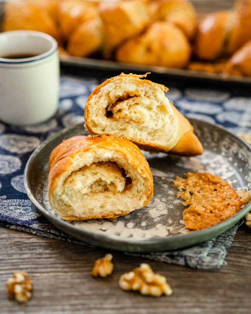 A Kifli walnut nut roll cut in half showing the nut filling swirled throughout sitting on a gray plate over a blue paisley napkin over a wooden board with walnuts spread in the front. A tray of rolls and a cup of coffee sit in the back.