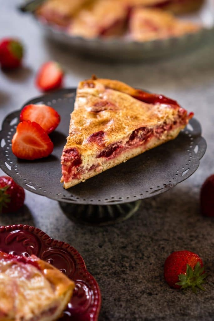 Side view of a slice of Kuchen showing a layer of strawberries over a crust and topped with custard sitting on a small gray cake stand. Strawberries are scattered around and a partial view of the whole kuchen in a metal pie tin sits in the background.