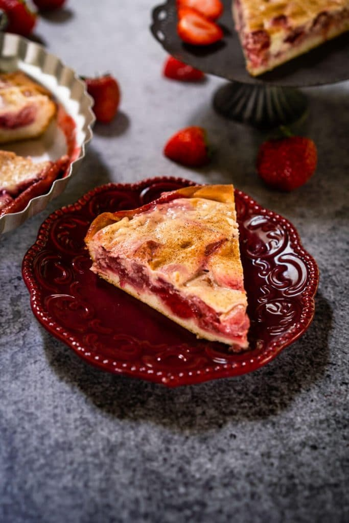 Angled view of a slice of Kuchen showing a layer of strawberries over a crust and topped with custard on a maroon plate. Strawberries are scattered around and a partial slice on a gray stand and the whole dessert in a pie tin is in the background on a gray background.