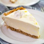 Close up side view of a slice of Lemon Icebox Pie. The slice has a thick graham cracker crust topped with a cool creamy layer and topped with a star of cool whip topping. The slice sits on a white plate over a blue napkin.