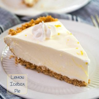 Close up side view of a slice of Lemon Icebox Pie. The slice has a thick graham cracker crust topped with a cool creamy layer and topped with a star of cool whip topping. The slice sits on a white plate over a blue napkin and the recipe title is in the left bottom corner.