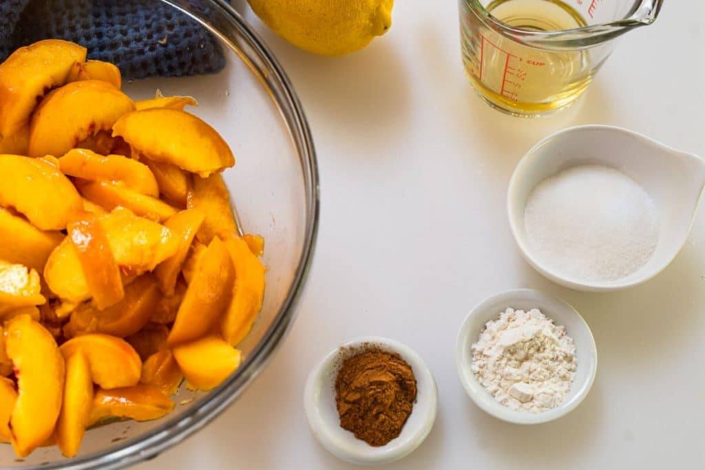 The ingredients used to make the peach filling in the peach crisp recipe including sliced peaches, cinnamon, flour, sugar, apple juice, and lemon juice.