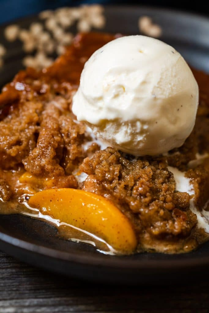 Top-down shot of a piece of peach crisp sitting in a dark gray bowl with vanilla ice cream melting down the side.