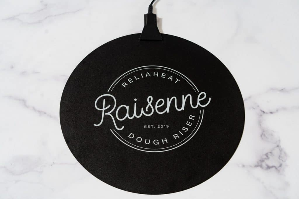A photo of the Raisenne Dough Riser on a marble background.