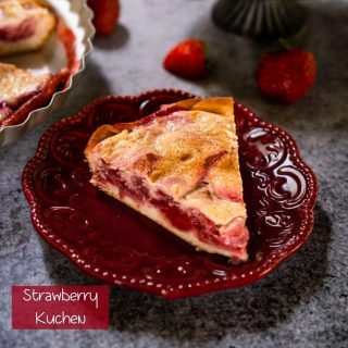 "Angled view of a slice of Kuchen showing a layer of strawberries over a crust and topped with custard on a maroon plate. Strawberries are scattered around and a partial slice on a gray stand and the whole dessert in a pie tin is in the background on a gray background. The title ""Strawberry Kuchen"" appears in the bottom left corner"