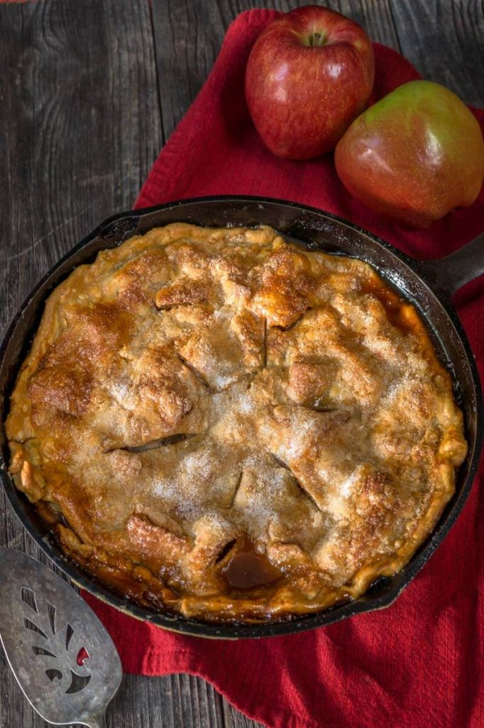 Top down view of an apple rhubarb pie baked in a cast-iron skillet sitting over a red napkin. Fresh apples are in the background and an antique pie server in the front.