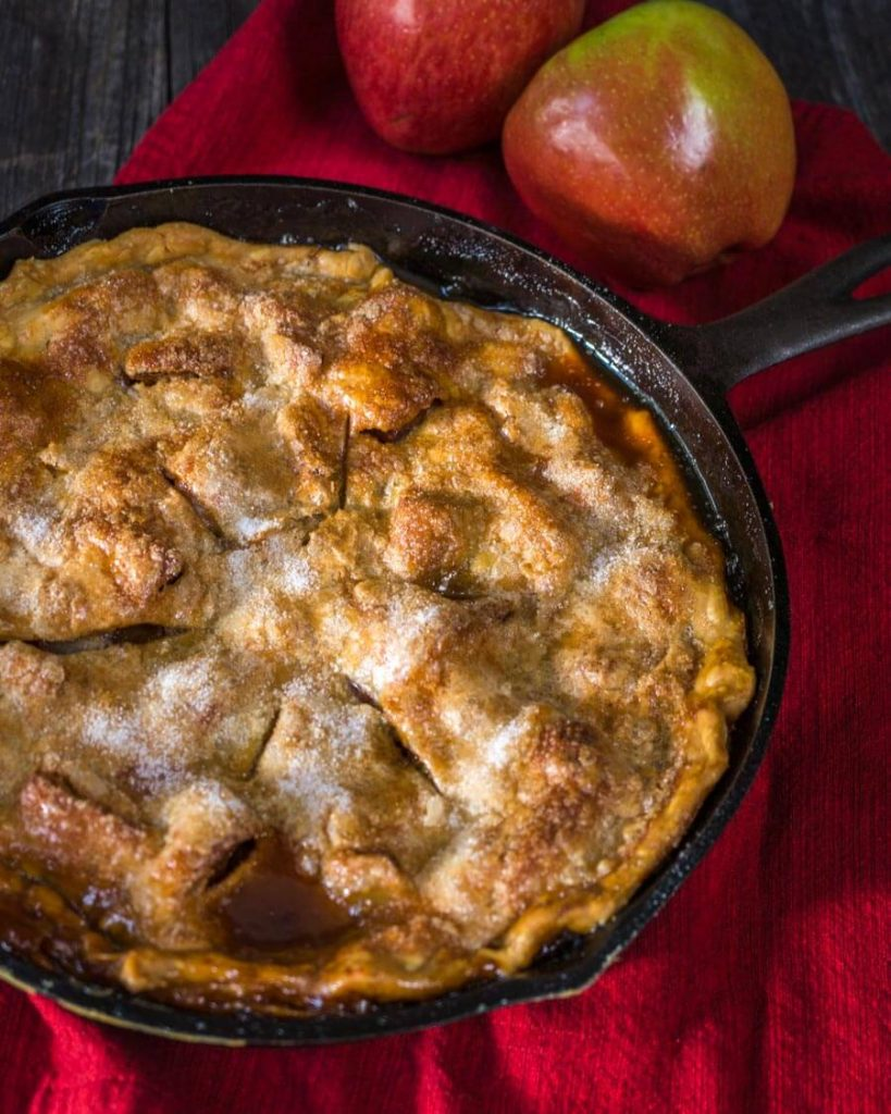 Top down view of an apple rhubarb pie baked in a cast-iron skillet sitting over a red napkin. Fresh apples are in the background.