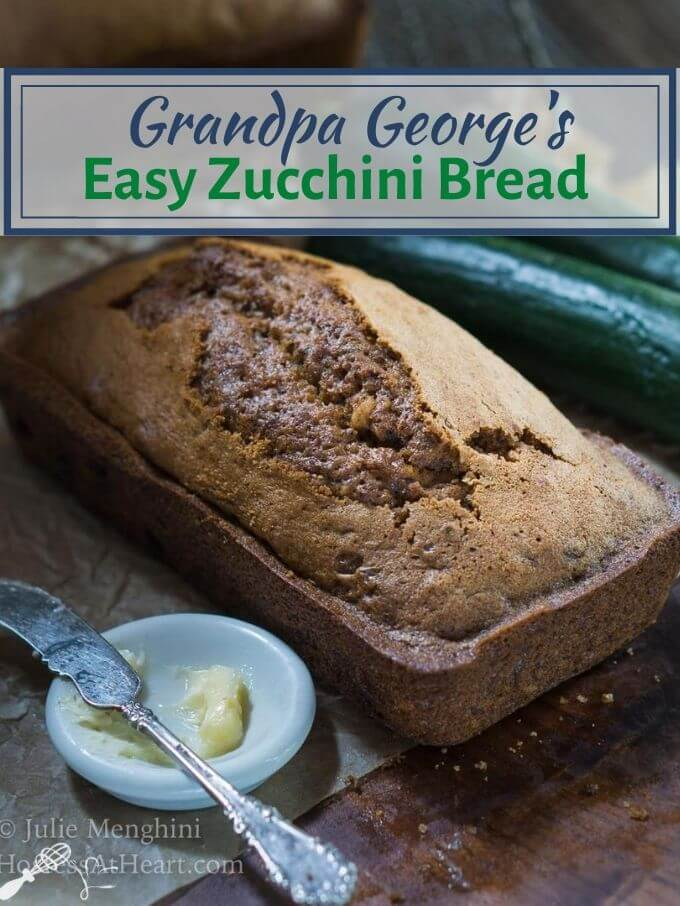 "An angled loaf of bread with two fresh zucchini's sitting in the back. A white dish with butter and an antique knife sit in the front. The title ""Grandpa George's Easy Zucchini Bread"" runs across the top."