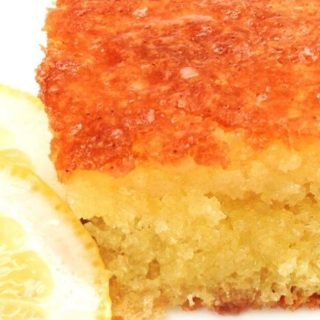 Close-up table view of a piece of lemon olive oil cake with slices of fresh lemon sitting off to the side.