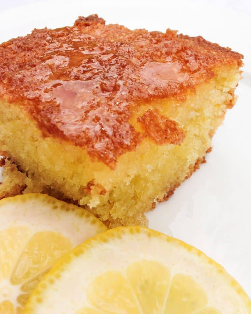 Front angled view of a piece of Lemon Olive Oil Cake with slices of fresh lemon sitting in the front.
