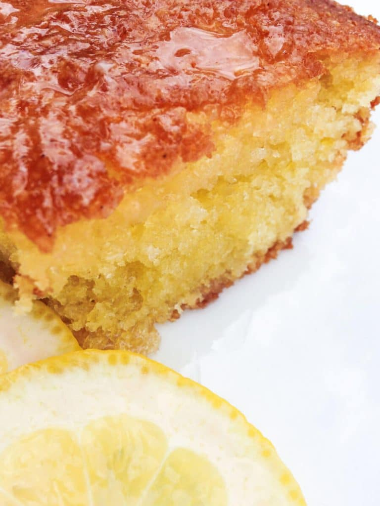 Front angled close-up view of a piece of Lemon Olive Oil Cake with slices of fresh lemon sitting in the front.
