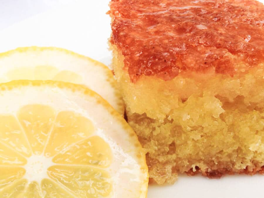 Front angled view of a piece of Lemon Olive Oil Cake with slices of fresh lemon sitting on the side.