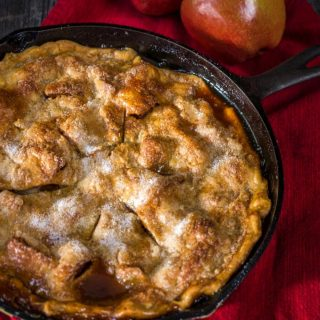 Top down view of a apple rhubarb pie baked in a cast-iron skillet sitting on a red napkin. Fresh apples sit in the background.