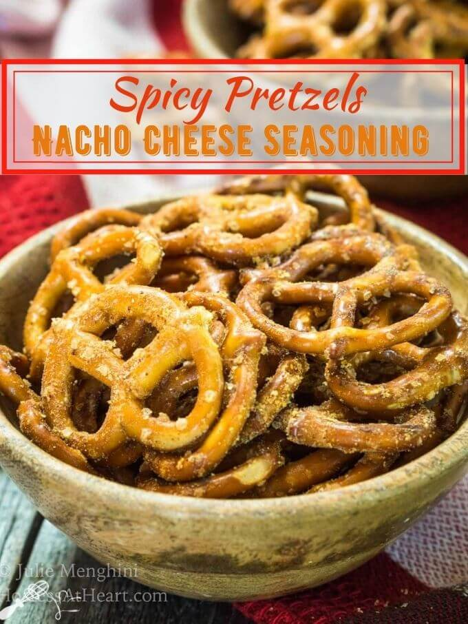 "Side view of spicy pretzels, dotted with seasonings in a wooden bowl over a red checked napkin. The title ""Spicy Pretzels Nacho Cheese Seasoning"" runs across the top."