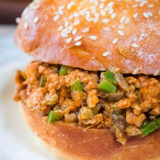 Close-up sideview of a turkey sloppy joe dotted with green pepper in a sesame seed bun sitting on a light blue plate.