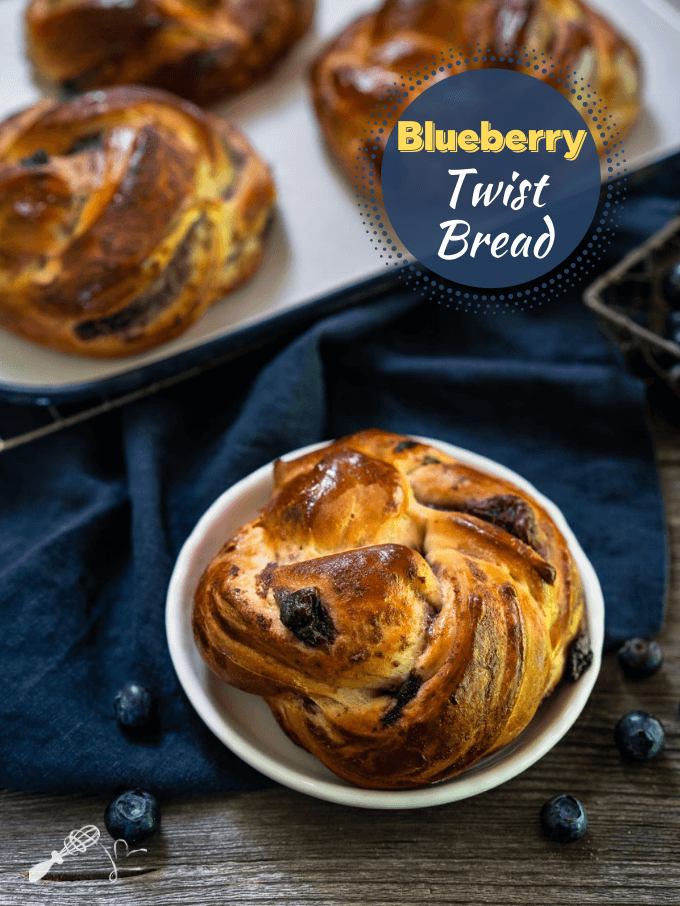 "Top down view of a blueberry twist roll sitting on a white plate over a blue napkin over a wooden background. Blueberries are scattered around the plate with more rolls in the background. The title ""Blueberry Twist Bread"" is in the upper right corner."