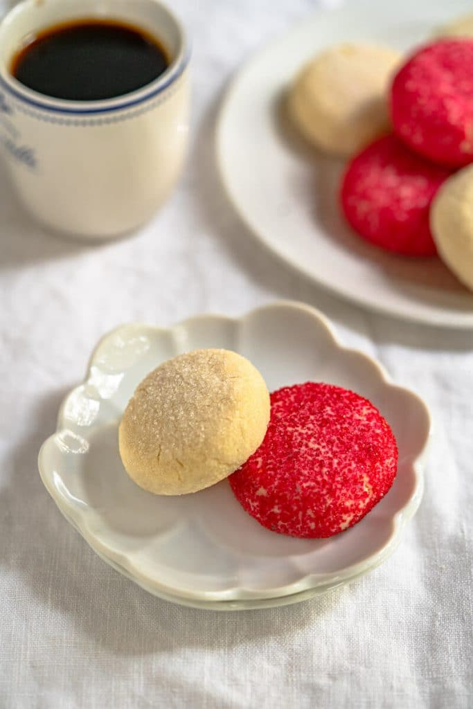 Angled view of a small white dish holding a red and a white decorated butter cookie with a cup of coffee and a plate of cookies in the background.