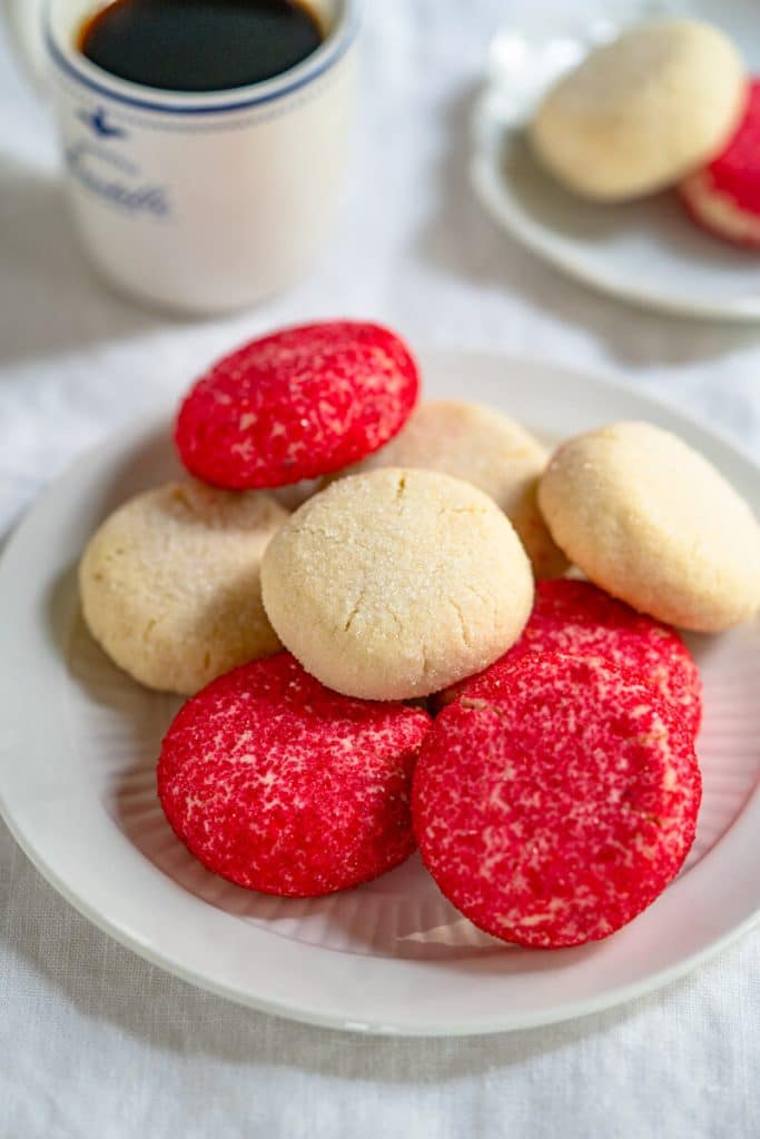 A plate of red and white decorated butter cookies with a cup of coffee and another plate holding two cookies in the background.