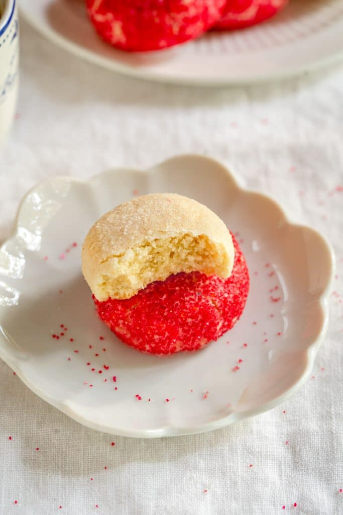 Side view of a white dish holding butter cookie decorated with red sprinkles with a butter cookie decorated with white sugar sitting on top of it with a bite out of it. A plate of cookies sit in the background.