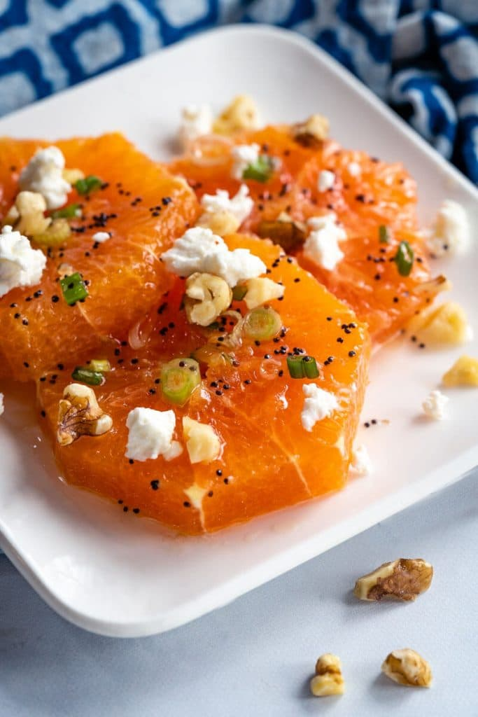 White dish filled with sliced oranges drizzled with a poppyseed vinaigrette and garnished with feta, walnuts, and sliced green onions.