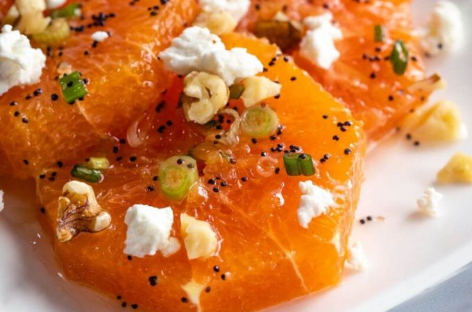 Close-up angle shot of a white plate holding fresh orange slices drizzled in a poppyseed vinaigrette and garnished with feta, sliced green onions, feta, and chopped walnuts.