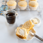 Top down photo of a muffin cut in half on a white plate with an antique knife propped against the plate next to a cup of coffee and a pat of butter. A cooling rack full of muffins sit in the background.