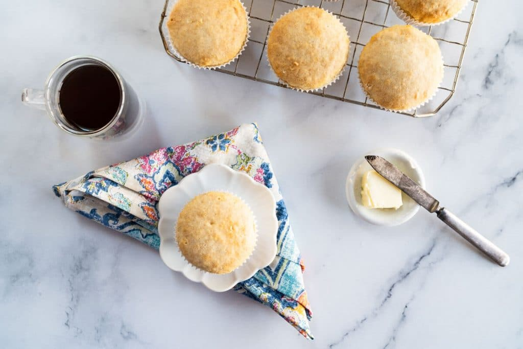 Top down photo of a muffin on a white plate over a multi-colored napkin next to a cup of coffee and a pat of butter. A cooling rack full of muffins sit in the background.