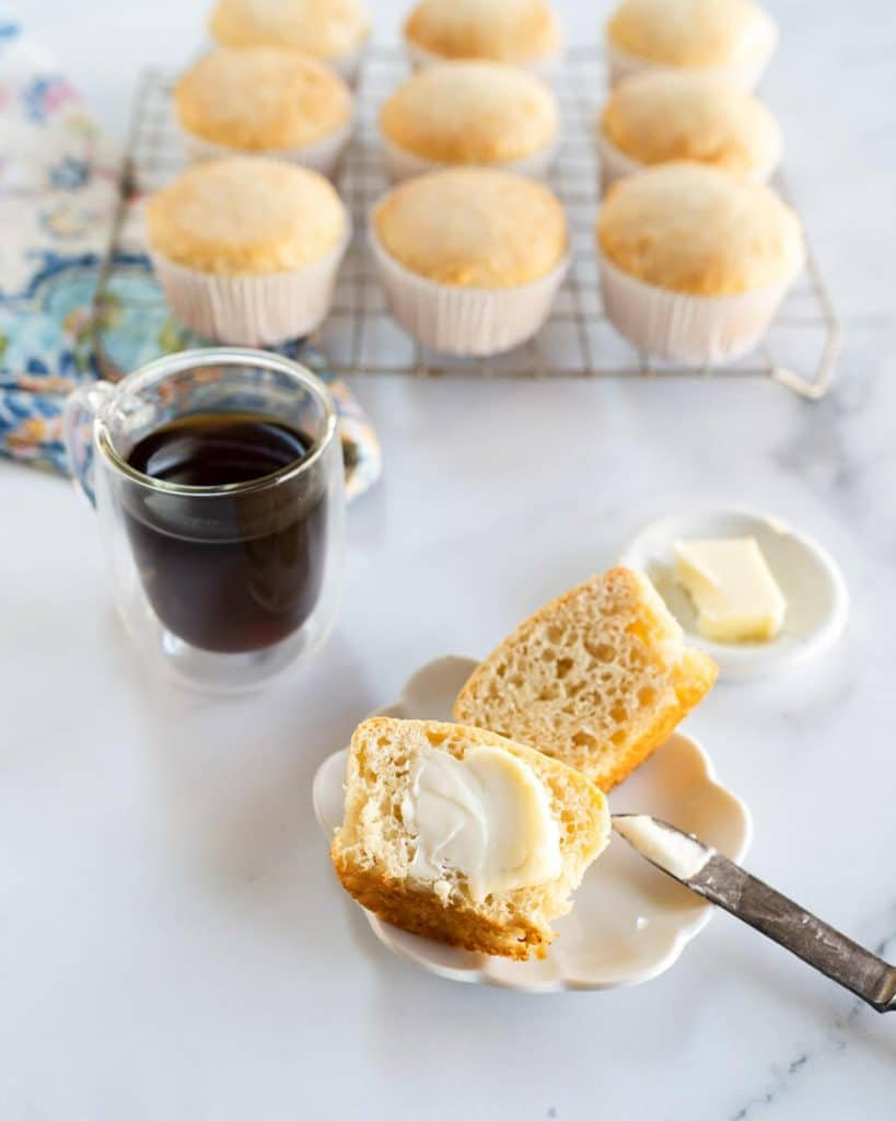 Top down photo of a muffin cut in half on a white plate over a multi-colored napkin next to a cup of coffee and a pat of butter. A cooling rack full of muffins sit in the background.