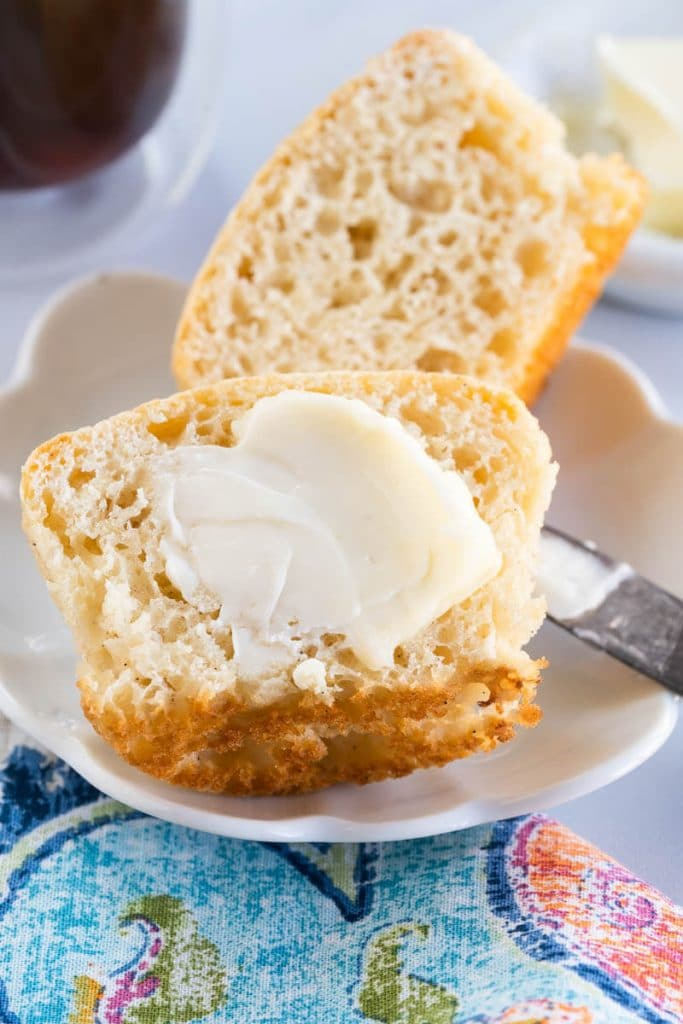 Close up of a vanilla muffin cut in half and slathered with butter.