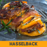 Butternut squash sliced and baked with apple, bacon, and rosemary on a metal plate.