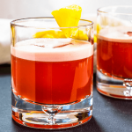 Closeup Sideview of two rocks glasses filled with a Campari Drink and garnished with pineapple.