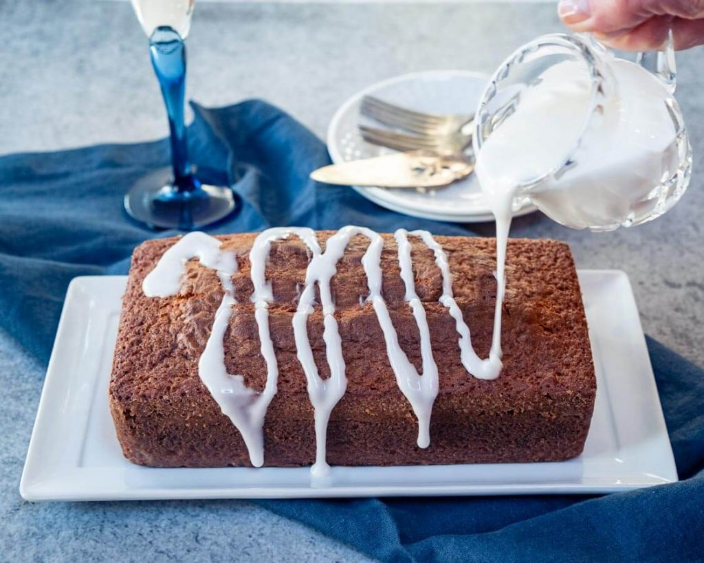 A loaf of champagne cake with a sugar glaze drizzling over the top sitting on a white plate over a blue napkin.