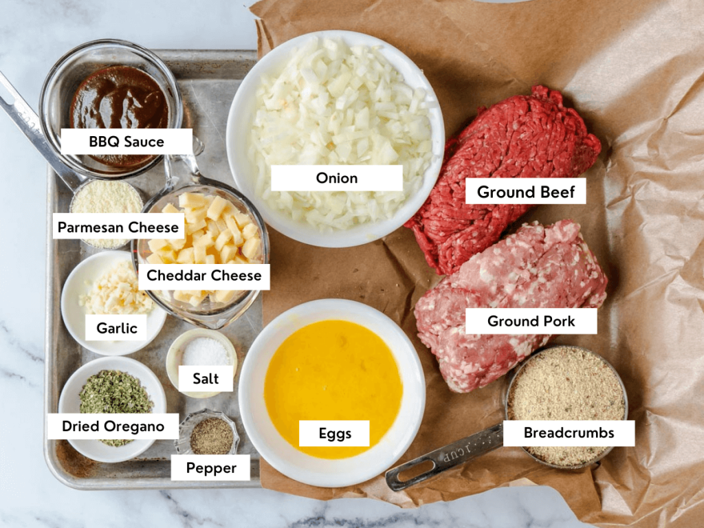 Top down view of the ingredients used in a cheese stuffed meatloaf including ground pork, ground beef, breadcrumbs, eggs, dried oregano, salt, pepper, garlic, cheddar cheese, onion, and garlic.
