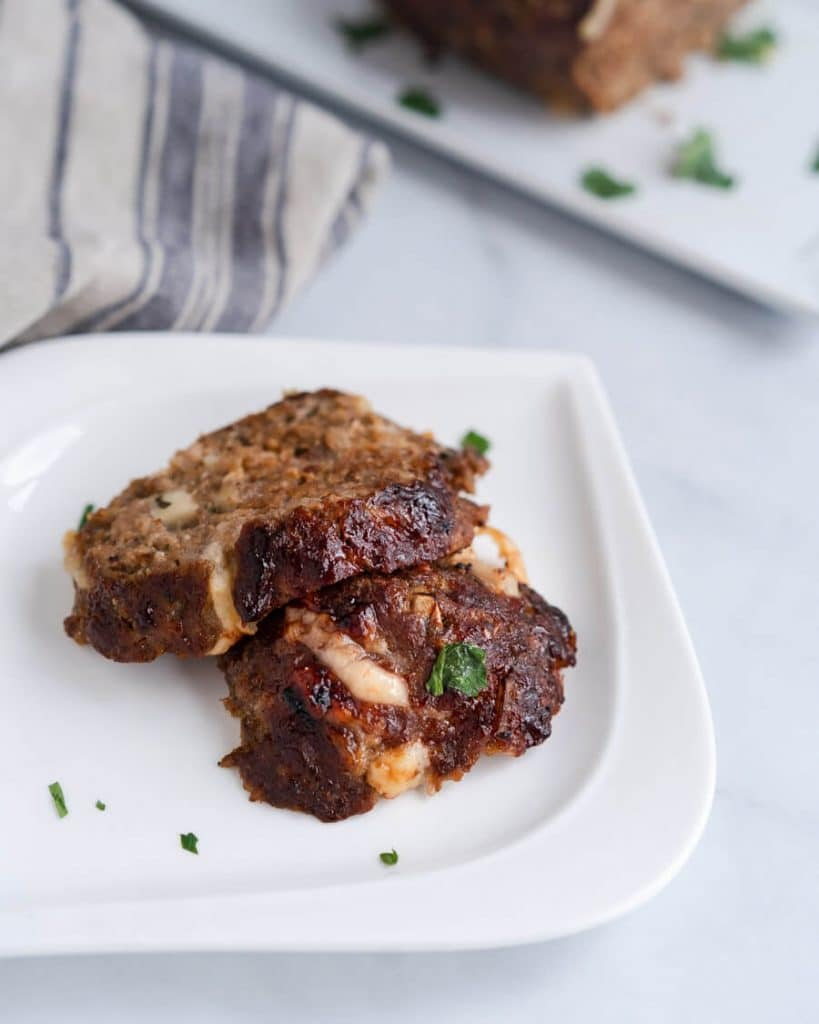 Top down photo of two slices of Cheese Stuffed Meatloaf sitting on a white plate. The plate is garnished with fresh parsley and sits on a blue stripped napkin.