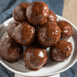 Side view of a stack of chocolate balls sitting on a white cake stand.