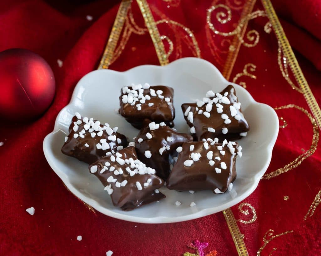 Top down view of chocolate covered Reindeer Food pretzel bites garnished with pearl sugar sitting on a white plate over a red napkin net to Christmas bulbs. A second plate sits in the background.