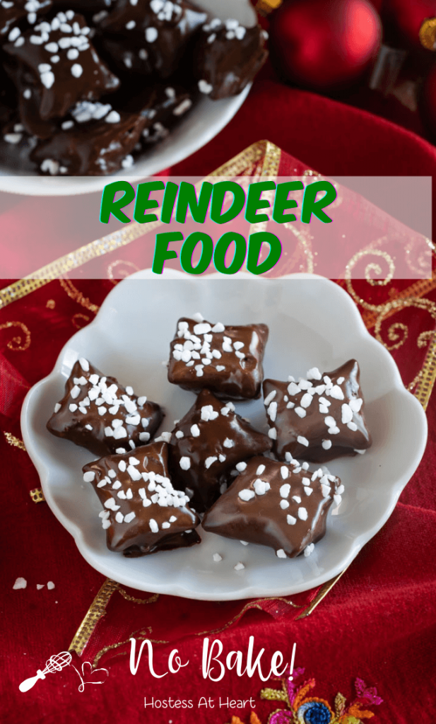 Top down view of chocolate covered Reindeer Food Recipe using pretzel bites garnished with pearl sugar sitting on a white plate over a red napkin net to Christmas bulbs. A second plate sits in the background.